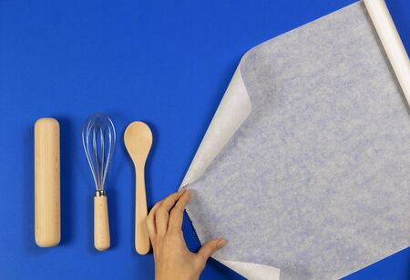 Woman hands roll baking paper. Wooden spoon, rolling pin and balloon whisk on blue background. Top view
