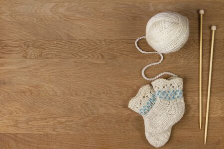 Knitting background. Wooden knitting needles, ball of yarn and small wool knitted socks on wooden background 写真素材