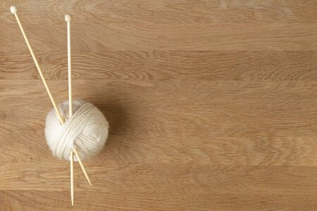 Wooden knitting needles and ball of yarn on wood background. Top view 写真素材