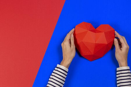 Female hands holding red polygonal heart on blue and red background. Top view