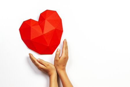Hands holding red polygonal paper heart shape over white background.
