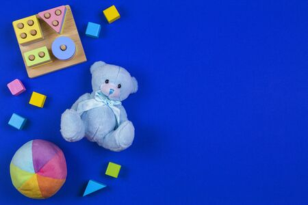 Baby kids toys background. Blue teddy bear, stacking pyramid tower, shape color recognition puzzle stacker on navy blue background Stock Photo
