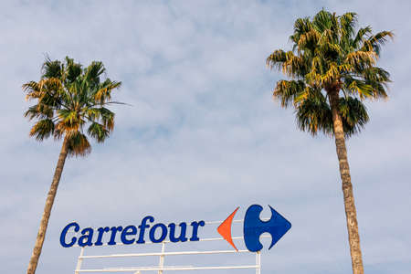 Finestrat, Spain - March 5, 2020: Carrefour logo on Carrefour supermarket with blue sky and palms background