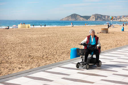 Benidorm, Spain - February 25, 2020: Woman with mobility scooter in Levante beach area in Benidorm, Spain