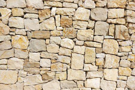 Masonry wall of stones with irregular pattern texture background Stock Photo