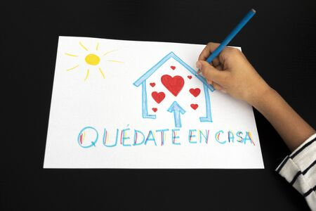 Coronavirus quarantine in Spain. Kid hand draw picture with spanish words Quedate en casa - Stay at home