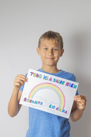Coronavirus pandemic self quarantine in Spain. Kids at home holding pictures with spanish words Quedate en casa - Stay at home and Todo va salir a bien - Everything will be fine