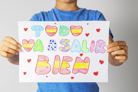 Coronavirus pandemic self quarantine in Spain. Kids at home drawing pictures with spanish words Todo va salir a bien - Everything will be fine