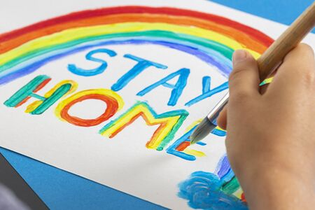 Kid painting during quarantine at home. Rainbow with words Stay at home. Social media campaign for coronavirus prevention Banque d'images