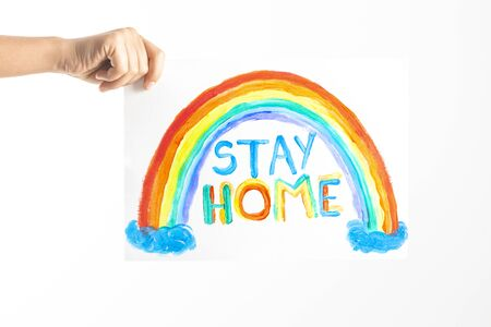 Kid hand holding drawing picture with colorful rainbow and words Stay home. Social media campaign for coronavirus prevention
