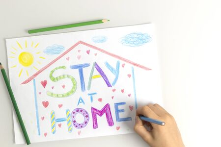 Quarantine at home during coronavirus pandemic. Kid hand drawing with coloring pencils picture with words Stay at home. Social media campaign for coronavirus prevention