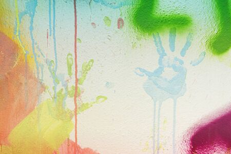 White plastered wall with colorful drips, flows and paint sprays. Handprints on white wall background
