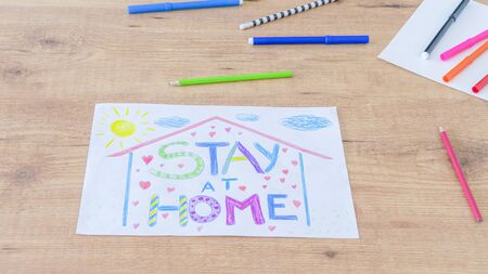 Quarantine at home during coronavirus pandemic. Kid drawing picture with words Stay at home and colored pencils on wooden table. Social media campaign for coronavirus prevention