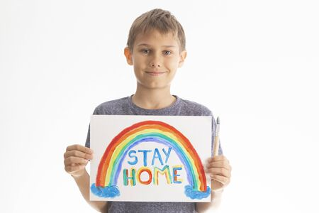 Kid holding drawing picture with rainbow with words Stay at home. Social media campaign for coronavirus prevention Banque d'images