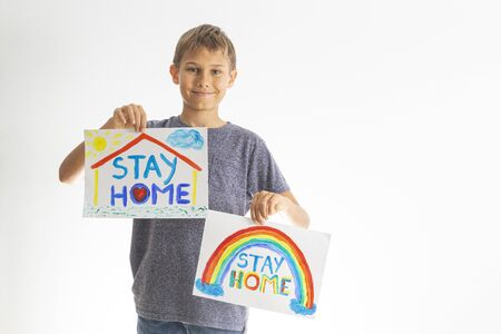 Kid holding drawing pictures with words Stay at home. Social media campaign for coronavirus prevention