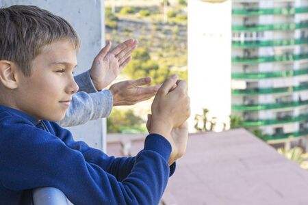 Family applauding medical staff from their balcony. People in Spain clapping on balconies and windows in support of health workers during the Coronavirus pandemic Stock Photo