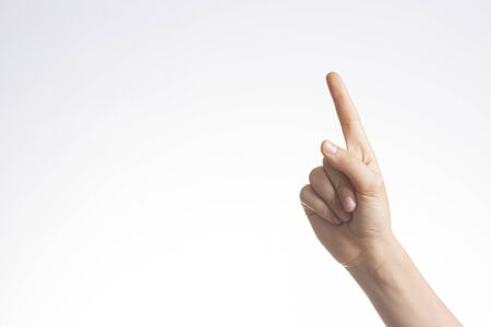 Hand pointing, shows number one gesture with index finger on white wall background. 版權商用圖片