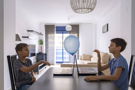 Children learning with laptop computer and play with balloon at home. Technology, education, online distance learning for kids. Stay at home entertainment Stock Photo