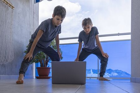 Kids with laptop doing sport exercises at home on balcony. Sport, healhty lifestyle, active leisure, stay at home, online learning, online training
