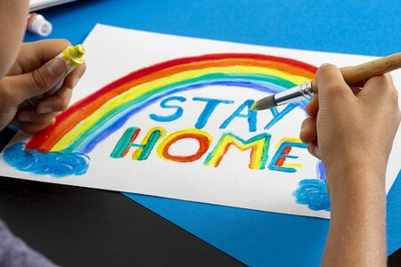 Boy painting during quarantine at home. Rainbow with words Stay at home. Social media campaign for coronavirus prevention Imagens