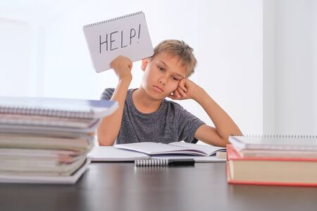 Upset tired preteen child sitting at the table, doing his homework among pile of books. Word Help is written on open notebook