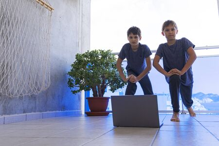 Children with laptop computer doing sport exercises at home on balcony. Sport, healhty lifestyle, active leisure, stay at home, online learning, online training
