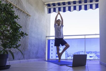 Boy doing sport exercises, practicing yoga on balcony. Sport, healhty lifestyle, active leisure at home