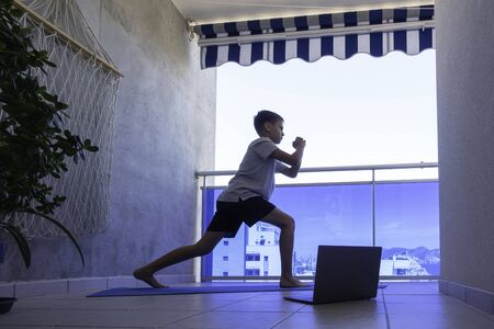 Boy with laptop computer doing sport exercises on balcony. Sport, healhty lifestyle, active leisure at home