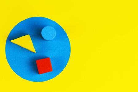 Wooden colorful blocks on geometric yellow blue background. Natural educational zero waste wood toys. Top view Фото со стока