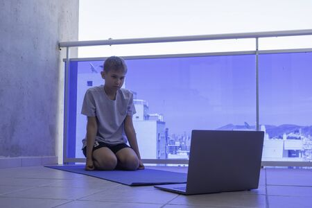 Boy looking online workout on laptop computer and doing sport exercises on balcony. Sport, healhty lifestyle, active leisure at home Фото со стока