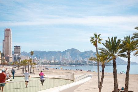 Benidorm, Spain - February 25, 2020: People enjoy sunny day in popular spanish resort Benidorm, Alicante, Spain