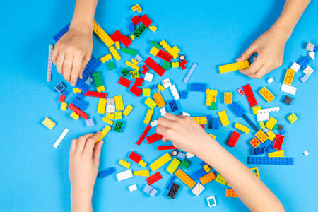 Vilnius, Lithuania - February 23, 2019. Children hands play with colorful lego blocks on the table Редакционное