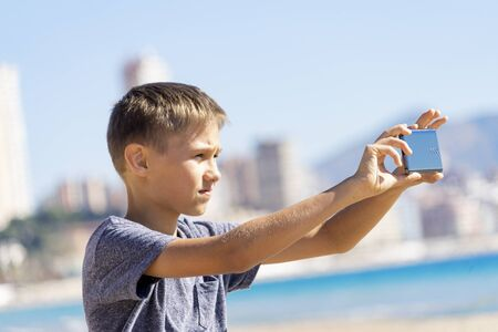 Boy taking photos using digital camera of mobile smartphone in city beach at sunny day