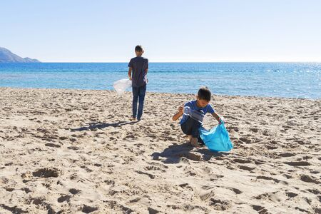 Volunteers cleaning beach from plastic. Boys walking on the beach and picking up plastic bottles trash and putting into plastic bag for recycle Фото со стока