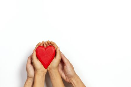 Adult and kid hands holding red heart over white background. Love, healthcare, family, insurance, donation concept Фото со стока