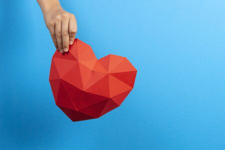 Kid hand holding red polygonal paper heart shape over light blue background