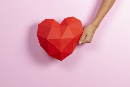 Hand holding red polygonal paper heart shape on light pink background