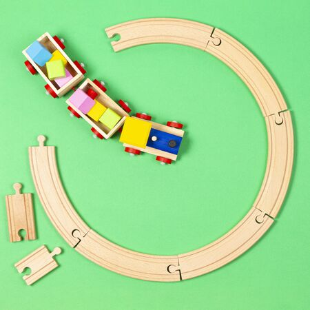 Toy train moves on round wooden railways on light green background. Top view Фото со стока