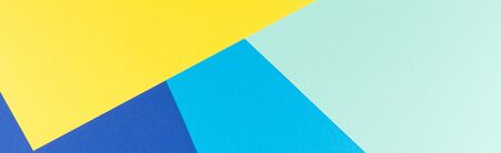 Color papers geometry flat composition background with yellow and blue tones.