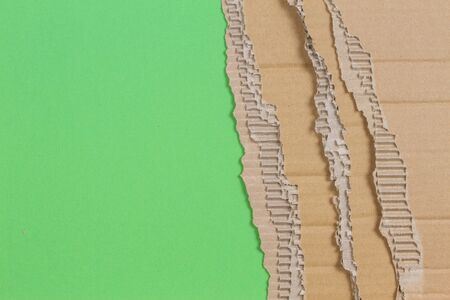 Piece of corrugated cardboard with torn paper edge on green background Фото со стока - 150471403