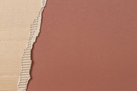 Brown corrugated cardboard ragged edge frame on brown background 스톡 콘텐츠