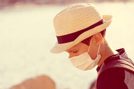 Boy with sun fedora hat and protective mask standing lowered head outdoors. Vacation, holiday, travel concept