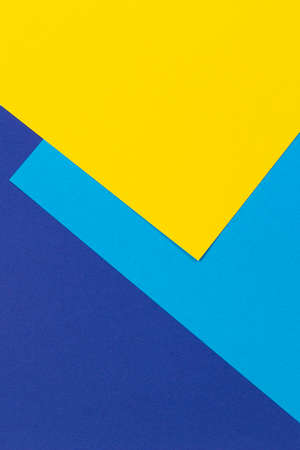 Creative abstract blue and yellow color geometric paper compositon background, top view