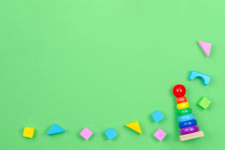 Kids toys background frame with baby stacking rings pyramid and colorful blocks on green background