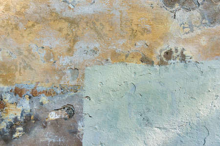 Old cracked weathered painted wall background texture. Light peeled plaster wall with falling off flakes of paint Stock Photo