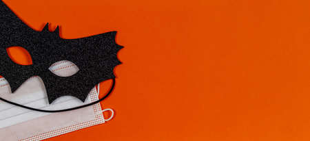 Black halloween eye mask and medical protective face mask on orange background