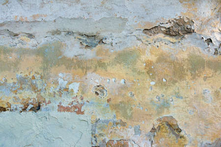 Old cracked weathered painted wall background texture. Light peeled plaster wall with falling off flakes of paint 写真素材