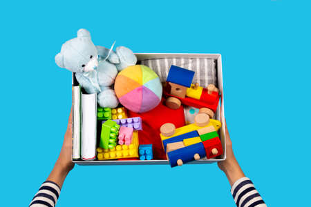 Donation concept. Kid hands with donate box with clothes, books and toys on light blue background. Top view