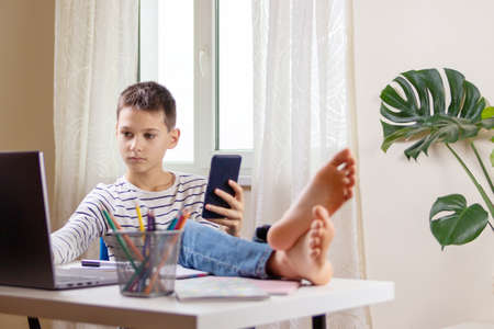 Kid distracting from online lesson or homework and playing video games, scrolling phone, texting on smartphone. Learning difficulties, online education, entertainment at home Stock Photo