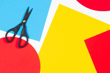 Colorful paper sheets and scissors on white desk background. Top view, copy space